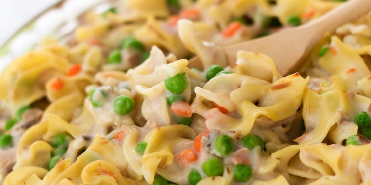 Cooked noodles with peas and carrots