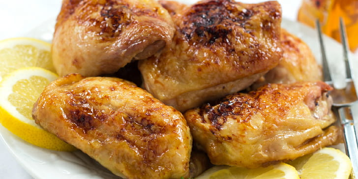 Five pieces of baked chicken on a white plate with 4 lemon slices and a meat fork with a jar of honey in the background