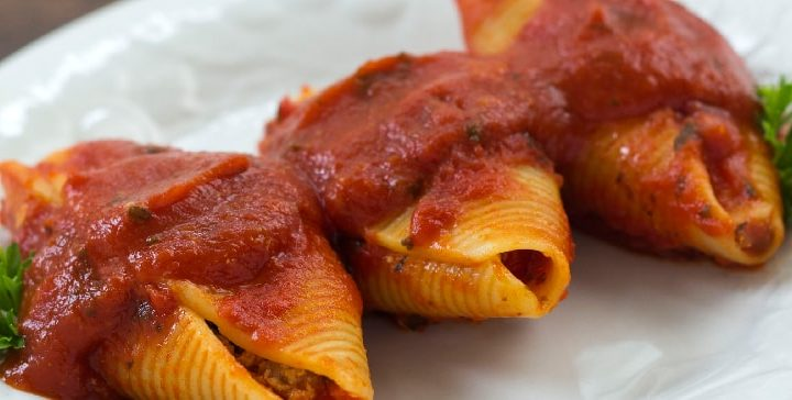 White plate with 3 jumbo pasta shells stuffed with beef and covered with spaghetti sauce, garnished with parsley