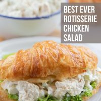 Chicken salad and lettuce on a croissant, all on a white plate. In the background is a bowl of chicken salad and more croisssants. Text is Best Ever Rotisserie Chicken Salad - Add Salt & Serve logo