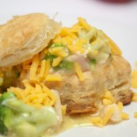 Biscuits with broccoli, chicken, and shredded cheddar cheese on a white plate