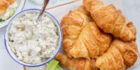 4 croissants on a plate next to a white bowl with a blue rim full of chicken salad, with a spoon handle sticking out, garnished with 2 celery sticks
