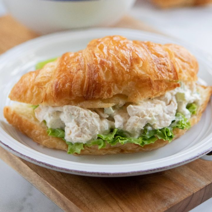 White plate with chicken salad on a bed of lettuce on a croissant, sitting on a brown table with a white bowl in the background