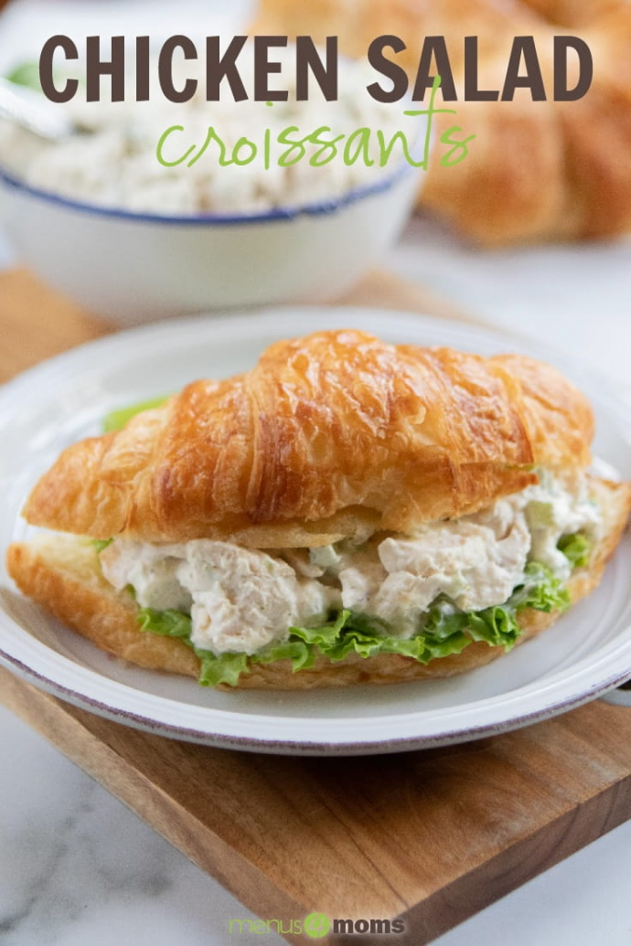 White plate with chicken salad on a bed of lettuce on a croissant, sitting on a brown table with a white bowl with a blue rim full of chicken salad with a spoon handle sticking out; text Chicken Salad Croissants Menus4Moms