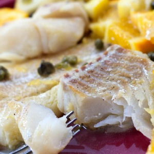 Cooked tilapia with capers and orange slices on top on a red plate with a fork; text Citrus Caper Tilapia Menus4Moms