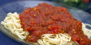 A pile of cooked spaghetti noodles covered with marinara sauce on a blue plate