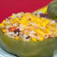 Green bell pepper on a white plate filled with rice, kidney beans, diced tomatoes, corn, and cheese beside another bell pepper all in front of a red background