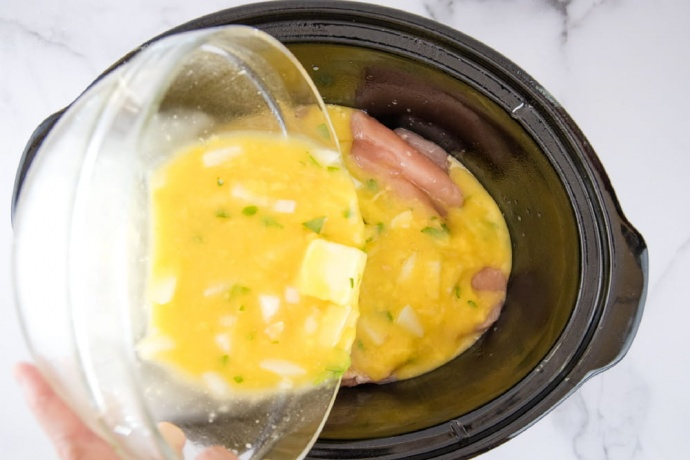 Mixture of butter, soup, broth, onions, and parsley being poured from a clear glass bowl over chicken breasts in a slow cooker.