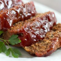 Slices of meatloaf with red glaze on a white plate garnished with fresh parsley