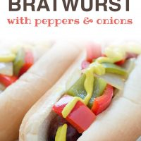 Bratwurst on a hotdog bun with mustard, diced red and green bell peppers and diced onions; text Grilled Bratwurst with Peppers and Onions Add Salt & Serve formerly Menus4Moms