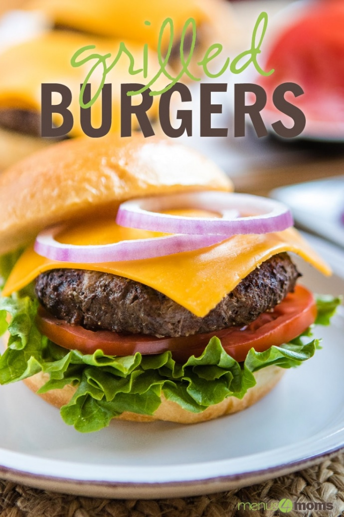 Lettuce, tomato slice, hamburger patty with melted slice of cheddar cheese, and two rings of red onion on a hamburger bun sitting on a white plate; text Grilled Burgers Menus4Moms