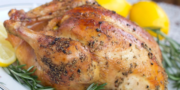 Roasted chicken covered with rosemary rub, garnished with fresh rosemary and lemon slices on a white plate