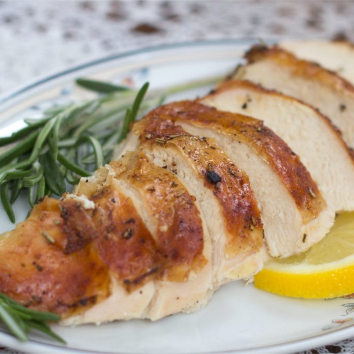 Sliced chicken breast on a white plate, garnished with rosemary and sliced lemons.