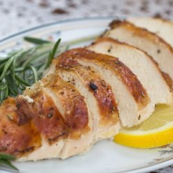 slices of roasted chicken garnished with fresh rosemary and lemon slices on a white plate