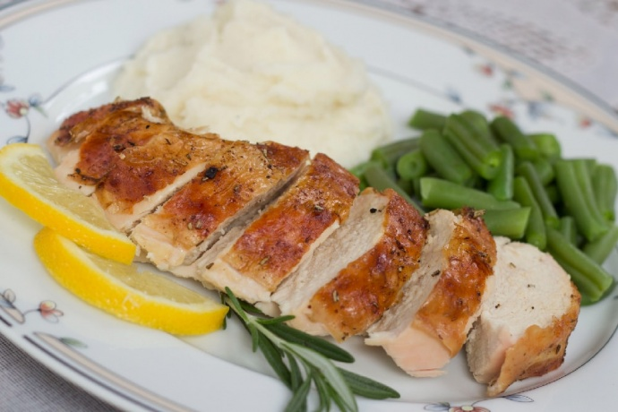 Slices of roasted chicken on a white plate with mashed potatoes and green beans, garnished with fresh rosemary and lemons