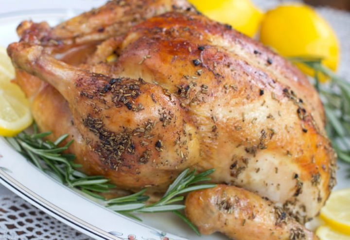 Roasted whole chicken on a white plate, garnished with rosemary and sliced lemon.