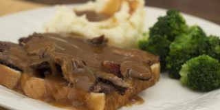 Photo of a slice of white bread with sliced roast beef and gravy, with mashed potatoes and gravy and cooked brocoli florets on a white plate
