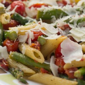 Cooked penne pasta, 1-inch pieces of asparagus, grape tomatoes, topped with a garnish of parmesan cheese on a white plate with blue and brown stripes with a fork in the background