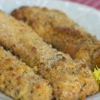 Three breaded chicken tenders on white plate; text Baked Parmesan Garlic Chicken Tenders Menus4Moms
