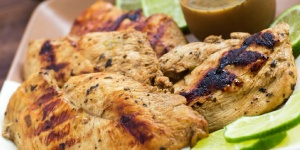 Grilled chicken breasts on a square brown plate with a clear glass cup of marinade and garnished with lime slices.