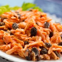Carrot Raisin salad on a white plate garnished with celery leaves