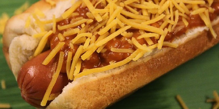 Hot dog in a bun, covered with chili and shredded cheddar cheese, with a green background.