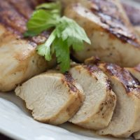 Sliced grilled chicken breast on a white plate, garnished with a sprig of parsley.