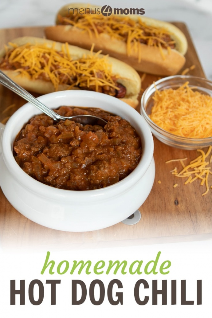 White bowl full of chili with a spoon sticking out. Two hot dogs in buns, covered with chili and shredded cheddar cheese. A small clear glass bowl with shredded cheddar cheese. All are on top of a square wooden cutting board on a white counter; text Homemade Hot Dog Chili Menus4Moms