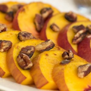 A white plate sits on a white lace tablecloth. On the plate are peach slices topped with chopped pecans. There is a fork in the background.