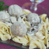Wide egg noodles and meatballs topped with a mushroom sauce on a purple plate, garnished with parsley