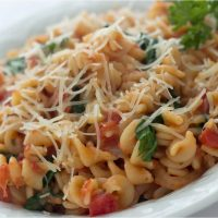 Spiral pasta mixed with diced tomatoes and spinach, topped with shredded parmesan cheese, on a white plate