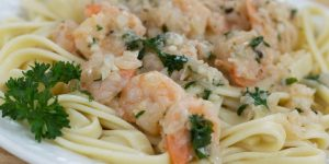White plate with shrimp, minced garlic, and parsley on a bed of fettuccine