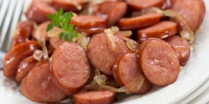 Sliced Kielbasa cooked with onion served on a white plate with a fork and garnished with a sprig of parsley