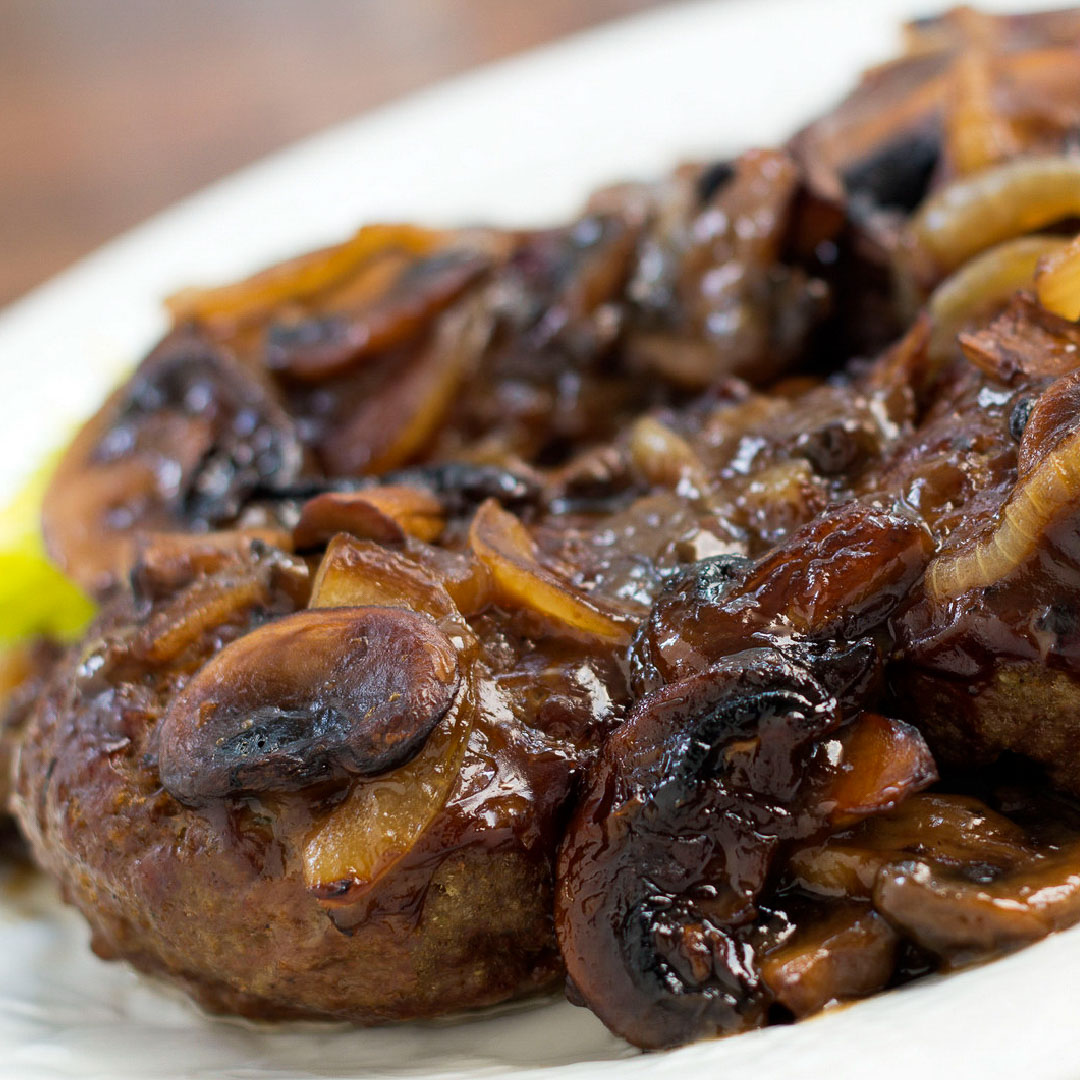 Hamburger patty covered with sliced mushrooms and onions and gravy.