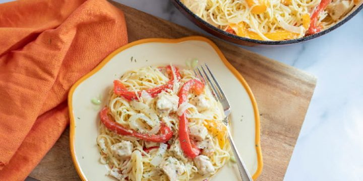 Strips of onion and red and yellow bell peppers with diced chicken on a bed of angel hair pasta on a white plate with a yellow rim. The plate is on a wooden cutton board on a white marble counter. There is an orange napkin beside the plate. At the top of the photo is part of a skillet with angel hair pasta, strips of red and yellow bell peppers, and diced chicken.
