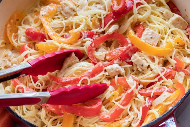 A pair of tongs in a skillet of sliced onions, red and yellow bell peppers, diced chicken, tarragon, and shredded mozzarella cheese.