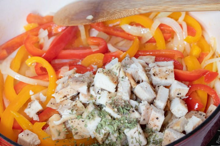 A wooden spoon stirring sliced onions and red and yellow bell peppers and diced chicken and tarragon in a skillet.