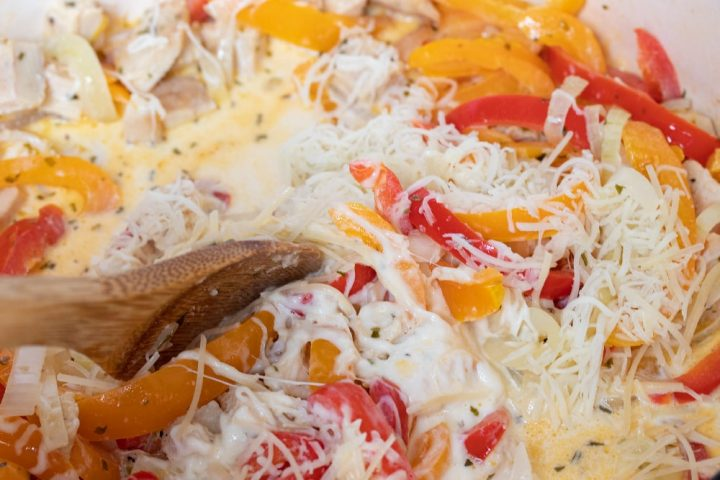 A wooden spoon stirring sliced onions and red and yellow bell peppers and diced chicken, tarragon, half and half, and shredded mozzarella cheese in a skillet.