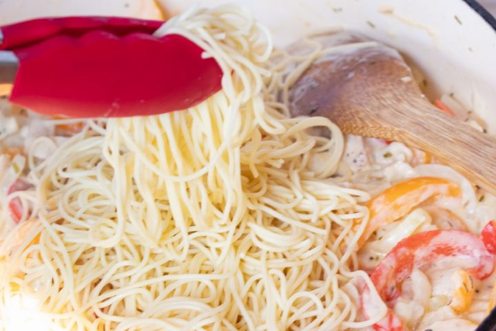 A wooden spoon stirring sliced onions and red and yellow bell peppers and diced chicken, tarragon, half and half, and shredded mozzarella cheese in a skillet. Cooked angel hair pasta is on top of the vegtables and cheese and a pair of red tongs is holding some of the pasta above the skillet.