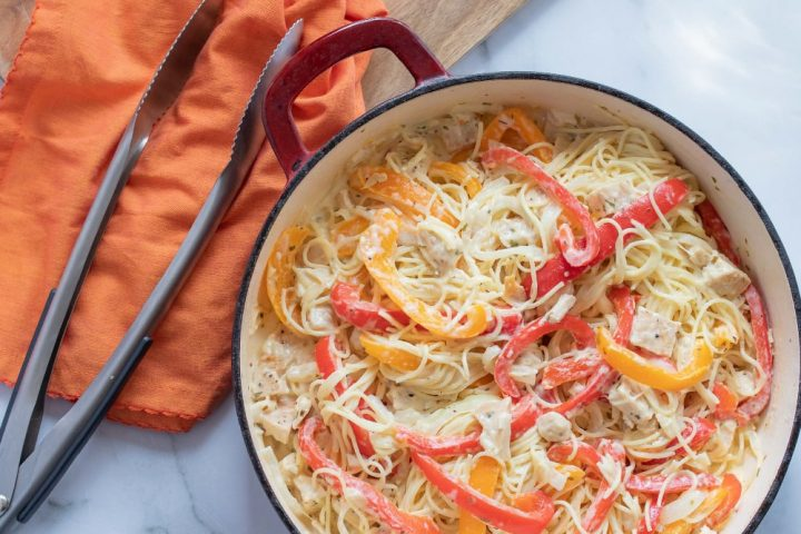 Strips of onion and red and yellow bell peppers with diced chicken on a bed of angel hair pasta, with melted mozzarella cheese, all in a skillet on a white marble counter. There are metal tongs and an orange napkin on a wooden cutting board in the top left corner of the photo.