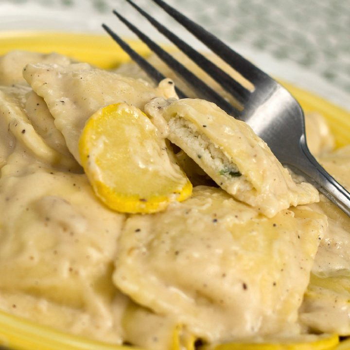 A yellow plate with cheese ravioli and slices of yellow squash covered with cheese sauce. There is a fork on top of the ravioli.