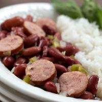 Slices of smoked sausage mixed with red beans, diced onions, and diced green bell pepper, beside a serving of rice. The food is in a white bowl with a fork and garnished with a sprig of parsley.