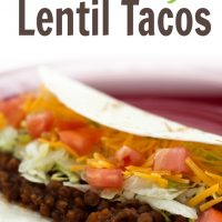 Folded tortilla with lentils, shredded lettuce, diced tomatoes, and shredded cheddar cheese on a red plate; text Healthy Lentil Tacos Menus4Moms