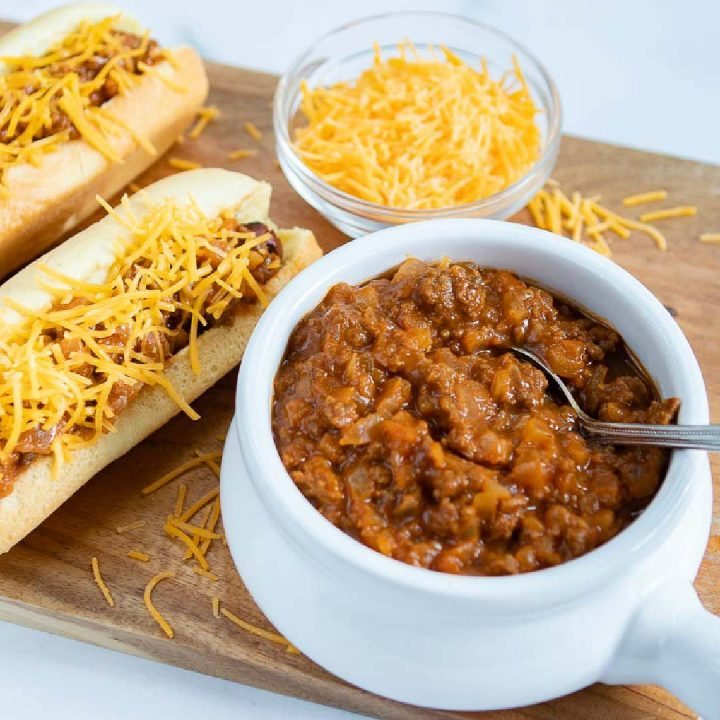 White bowl full of chili with a spoon sticking out. Two hot dogs in buns, covered with chili and shredded cheddar cheese. A small clear glass bowl with shredded cheddar cheese. All are on top of a square wooden cutting board on a white counter.