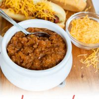 White bowl full of chili with a spoon sticking out. Two hot dogs in buns, covered with chili and shredded cheddar cheese. A small clear glass bowl with shredded cheddar cheese. All are on top of a square wooden cutting board on a white counter; text Add Salt & Serve fomerly Menus4Moms Homemade Hot Dog Chili