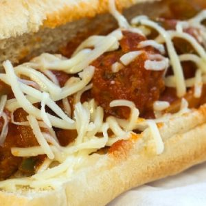 Meatballs, sauce, shredded mozarrella cheese, and strips of bell peppers on a hot dog bun, all on a white plate.