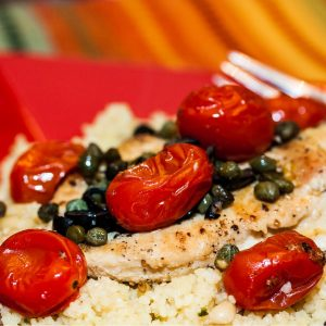 Chicken breast on a bed of couscous topped with capers, sliced black olives, and cherry tomatoes on a red plate with a fork.