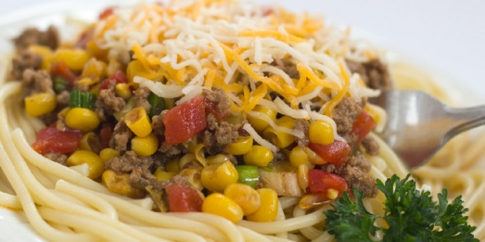 White plate with spaghetti noodles topped with ground beef, corn, tomatoes, sliced green onions, and shredded Mexican Blend cheese. There is fork sticking out of the food.