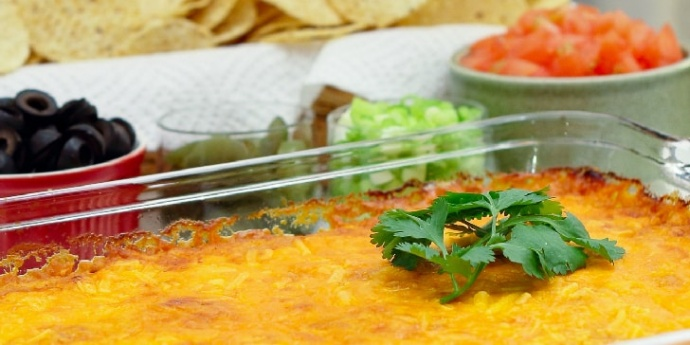 Clear glass casserole dish with beans topped with melted cheese and garnished with a sprig of cilantro. In the background is a red bowl of sliced black olives, a clear bowl of jalepeno slices, a clear bowl of diced green onions, a white bowl of diced tomatoes, and a basket of tortilla chips.