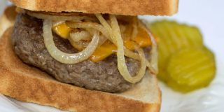 A hamburger patty topped with a slice of melted cheese and sauteed onion rings between two slices of toasted sourdough bread. The sandwich is on a white plate and garnished with pickle slices.